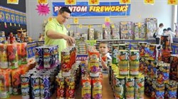 Bryan Kiger and his son Alex, 5, stack fireworks in the Phantom Fireworks store behind the Monroeville Mall in this file photo.