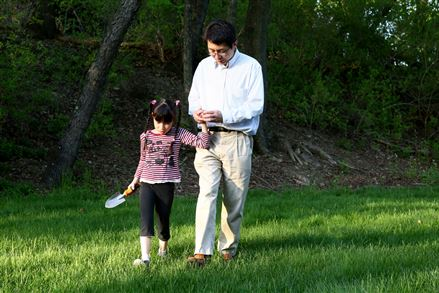 Tai Sing Lee walks with his daughter, Helen, in the backyard of the family's O'Hara home.