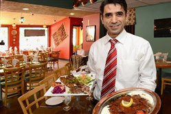 Istanbul Sofra owner Adnan Pehlivan offers lamb kabob (left)  and Iskender kabob at his Turkish restaurant in Regent Square in 2014.