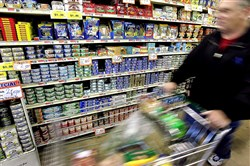 In this January 2006 photo, a shopper walks by cans of tuna in a grocery store in Des Plaines, Illinois. The chief executive of Bumble Bee Foods has stepped down, one week after he was indicted by a federal grand jury on charges that he conspired to fix the prices of packaged seafood.