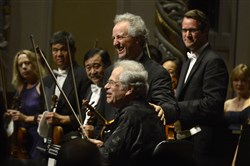 Violinist Itzhak Perlman, center foreground at the end of his performance, with Manfred Honeck, PSO music director at Cinema Serenade of the Pittsburgh Symphony Orchestra, at Heinz Hall on Sept. 12, 2015.