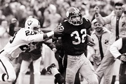 "Franco Harris eludes a tackle attempt by the Oakland Raiders' Jimmy Ware on the way to scoring the go-ahead touchdown during a play dubbed ""The Immaculate Reception."