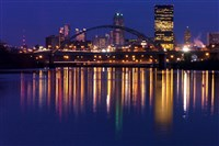 The lights from Pittsburgh's downtown skyline reflect in a calm Monongahela River, with the Birmingham Bridge in the foreground.
