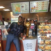 Cavaliers forward Tristan Thompson poses with the Larry O'Brien trophy and Tim Hortons employees.