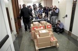 Journalists photograph the arrival of printed copies of U.S. President Donald Trump's fiscal year 2019 budget at the House Budget Committee on Capitol Hill February 12, 2018 in Washington, DC. The budget is expected to contain funding requests for the building of a wall on the southern border of the U.S., infrastructure projects, and increased military funding.