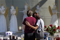People comfort each other at a public memorial for the victims of the Wednesday shooting at Marjory Stoneman Douglas High School, in Parkland, Fla., Friday, Feb. 16, 2018. Nikolas Cruz, a former student, was charged with 17 counts of premeditated murder.
