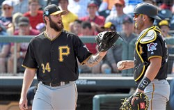 Pirates pitcher Trevor Williams talks with Francisco Cervelli as they take on the Braves during a spring training game in March.
