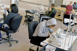 Workers in the stitching room of Thread International cut and sew a project in production in its new Homewood location.