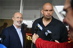 Pennsylvania Gov. Tom Wolf, left, and John Fetterman, Democratic nominee for lieutenant governor, answer questions from the media outside the Manchester Cafe on Wednesday in Manchester Township, Pa.