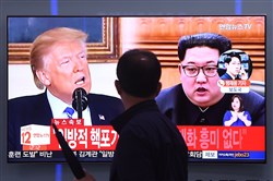 At a railway station in Seoul on May 16, a man walks past a television news screen showing North Korean leader Kim Jong Un and President Donald Trump.