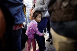 Nicole Hernandez holds onto her mother at the U.S.-Mexican border.