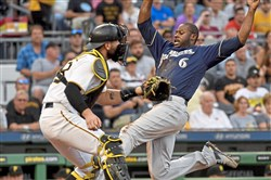 Brewers center fielder Lorenzo Cain scores behind Pirates catcher Francisco Cervelli in the third inning Tuesday, June 19, 2018 at PNC Park.