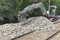 A Port Authority maintenance worker uses an excavator to move rocks to rebuild gabion baskets for retaining walls along the tracks at Logan Station in Bethel Park, part of more than 3 miles of light-rail tracks out of service after flood damage in June 2018, when this photo was taken.