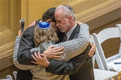Rabbi Jeffrey Myers, of Tree of Life Congregation, right, hugs Rabbi Jonathan Perlman, of New Light Congregation, and Rabbi Cheryl Klein, Dor Hadash Congregation, hug after thousands gathered on Oct. 28 at Soldiers & Sailors Memorial Hall for a vigil to remember the victims of the mass shooting at the Tree of Life Congregation synagogue.