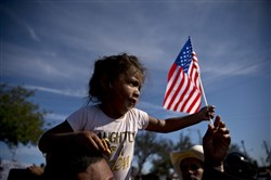 A migrant girl with a U.S. flag sits on the shoulders of a man marching with other migrants to the Chaparral border crossing in Tijuana, Mexico, on Nov. 25.