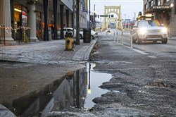 Water fills a large pothole in a downtown bike lane, Downtown.
