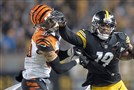Bengals free safety Jessie Bates is stiff armed by Steelers wide receiver JuJu Smith-Schuster during last year's season finale.