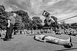 "The Jester flies through the air with a ""frog splash"" onto Del Douglas as referee Shawn Patrick prepares for the aftermath at Arsenal Park in Lawrenceville."