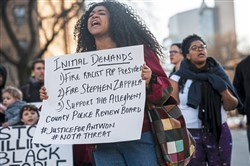 Mia Sterbini of Downtown holds up a sign with a list of demands as protesters take over the intersection of Fifth Avenue and Bigelow Blvd, Saturday, March 23, 2019, in Oakland. People in Pittsburgh are protesting the acquittal of Former East Pittsburgh police Officer Michael Rosfeld in the fatal shooting of Antwon Rose II on June 19, 2018.