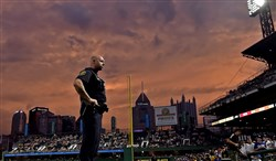 Pittsburgh Zone 4 police Officer Matt Schlick watches over the fans after storms clear from PNC Park Saturday night before the Pirates take on the Dodgers. The game was delayed for nearly two hours because of a thunderstorm warning issued for the area.