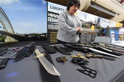 Lisa Farbstein, a Transportation Security Administration official, displays on Friday, Aug. 23, 2019 some of the many prohibited items that travelers have tried to bring through security at Pittsburgh International Airport. In the foreground is a knife that looks like a camouflaged gun.